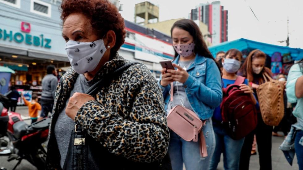 Brasil documenta caso de paciente que portó COVID-19 activo durante cinco meses - Personas con tapabocas hacen fila en un sector comercial de Sao Paulo, Brasil. Foto de EFE
