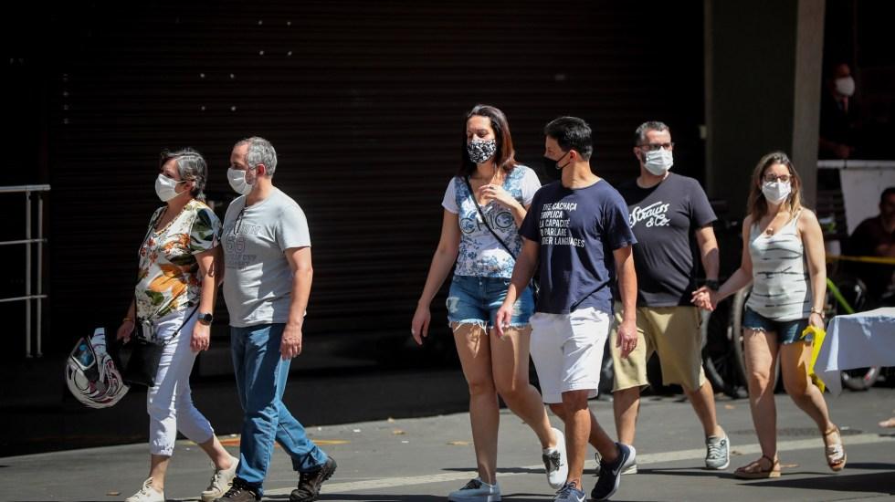 Alerta OPS riesgos en Latinoamérica por reapertura de vida social y pública ante COVID-19 - Personas con cubrebocas en calles de Sao Paulo, Brasil. Foto de EFE