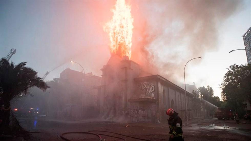 Sacude a Chile primer aniversario de protestas; dos iglesias de Santiago quedaron en llamas - Un grupo de bomberos trabaja en la extinción del incendio de la parroquia de la Asunción este viernes en los alrededores de la Plaza Italia de Santiago (Chile), EFE/Alberto Valdés