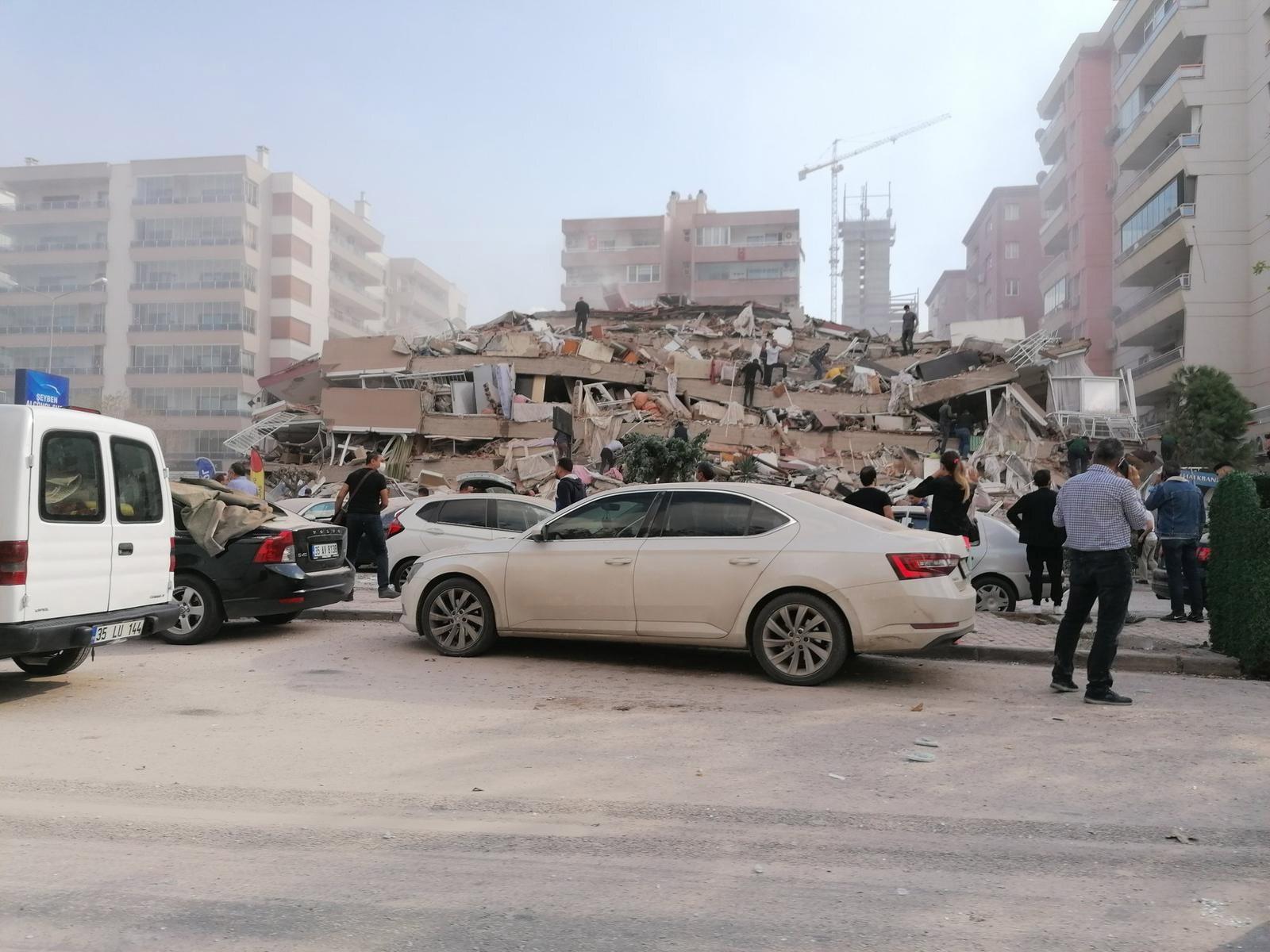 Personas alrededor de edificio colapsado tras terremoto en Esmirna, Turquía. Foto de EFE/EPA/Mehmet Emin Menguarslan.