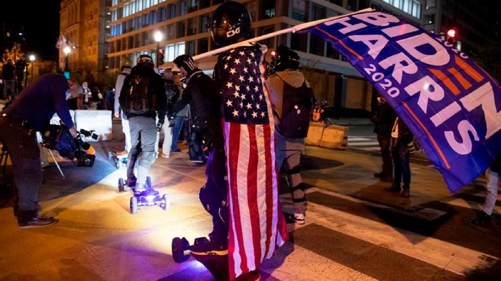 Nueva York cumple expectativas y vota de forma abrumadora por Joe Biden - Un hombre en patineta eléctrica lleva una bandera de Biden-Harris en la Black Lives Matter Plaza en Washington, DC. Foto EFE