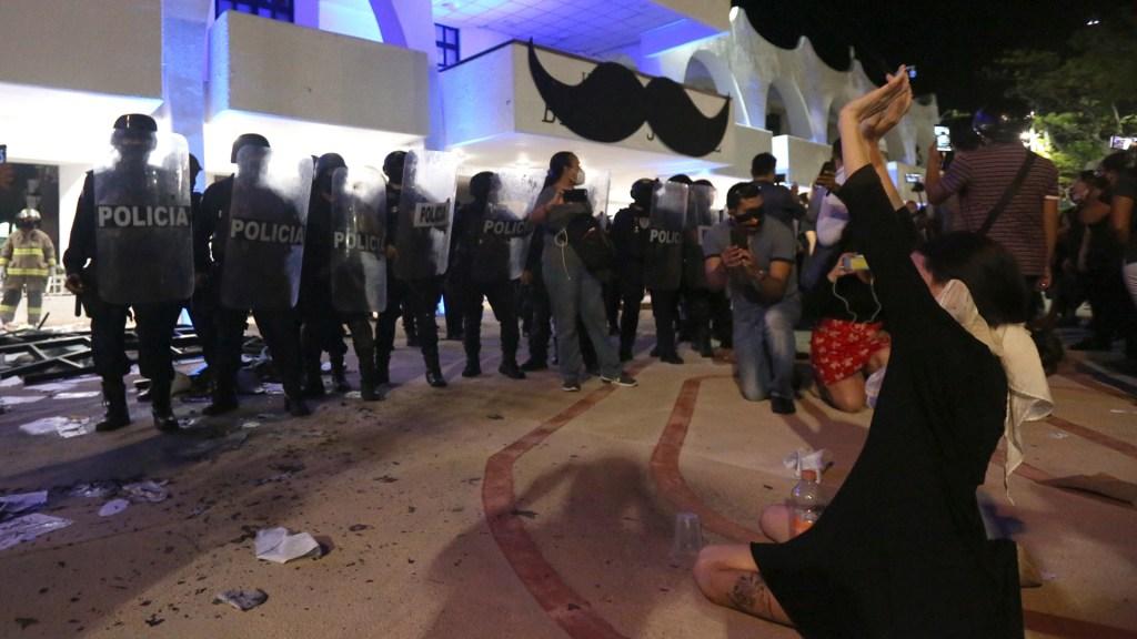 Condena AMLO agresiones contra manifestantes en Cancún; pide que haya justicia hoy mismo - Feministas se arrodillan frente a policías de Cancún después de que estos dispararan al aire para dispersar su manifestación. Foto de EFE