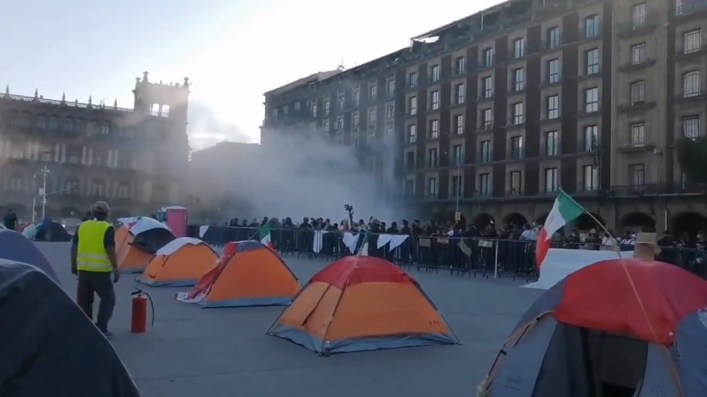 #Video Lanzan petardos contra quienes mantienen plantón en Zócalo capitalino - Humo en el Zócalo capitalino por lanzamiento de petardos contra manifestantes. Captura de pantalla