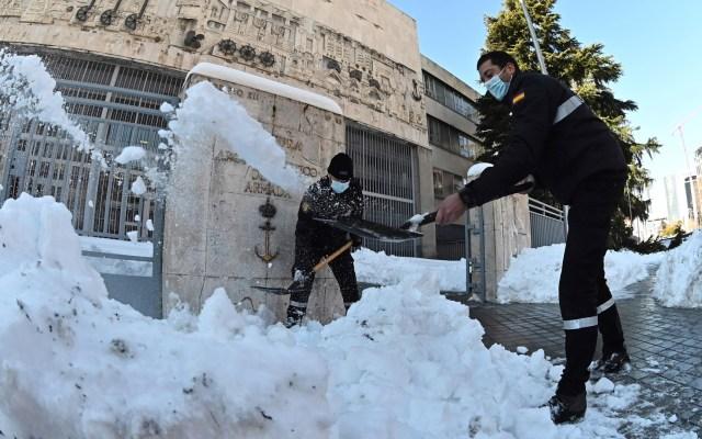 La nieve ya no es tan bonita ni divertida en Madrid después de diez días - Personas quitan con palas la nieve en España. Foto de EFE