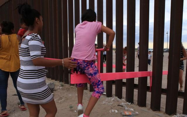 Subibaja en muro fronterizo entre México y EE.UU. gana mejor diseño del año - Niños y adultos utilizan subibajas de color rosa que, conjuntamente con niños estadounidenses, jugaron en la línea fronteriza que delimita a México y Estados en el punto fronterizo de Ciudad Juárez. Foto de EFE