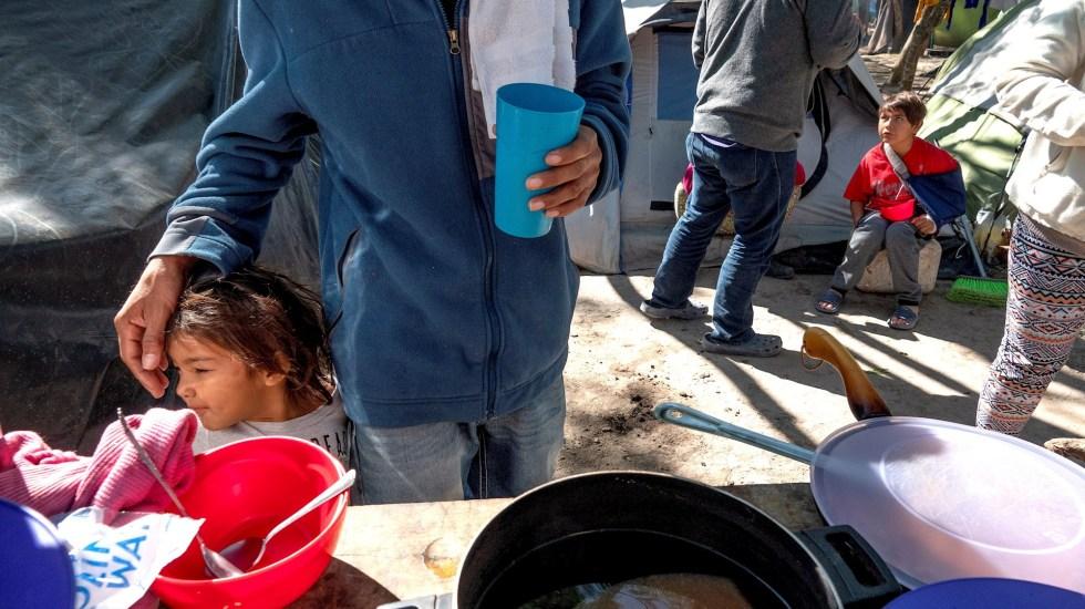 """Cifra de refugiados en el mundo es """"enorme"""", advierte ACNUR - Fotografía de archivo del 27 de febrero de 2020 que muestra al migrante salvadoreño Jesús Chávez mientras acaricia a su hija Carmen mientras cocina en el campo de refugiados de la fronteriza ciudad de Matamoros, Tamaulipas. La llegada a Estados Unidos de centenares de menores inmigrantes --más de 4 mil se encuentran bajo custodia de la Patrulla Fronteriza-- se ha convertido en otra prueba de fuego para la administración del presidente Joe Biden y está copando parte del debate político en el país. Como una"""