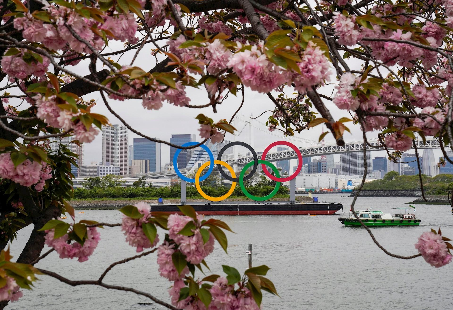 El Monumento del Anillo Olímpico instalado en el agua se ve a través de los cerezos en flor en Tokio, Japón, un día antes de que el país comience su cuenta regresiva de 100 días para la ceremonia de apertura de los Juegos Olímpicos de Tokio 2020. Foto de EFE / EPA / KIMIMASA MAYAMA.