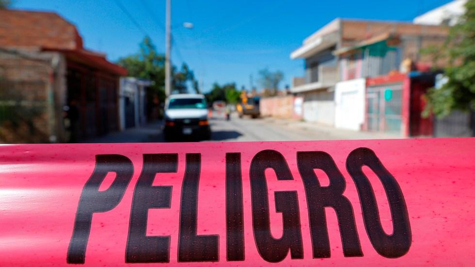 Suman 83 mil 826 homicidios dolosos en lo que va del sexenio - Cinta de peligro que marca el perímetro en la zona donde se encontró una fosa clandestina, con al menos 11 cuerpos, en Tonalá, Jalisco. Foto de EFE