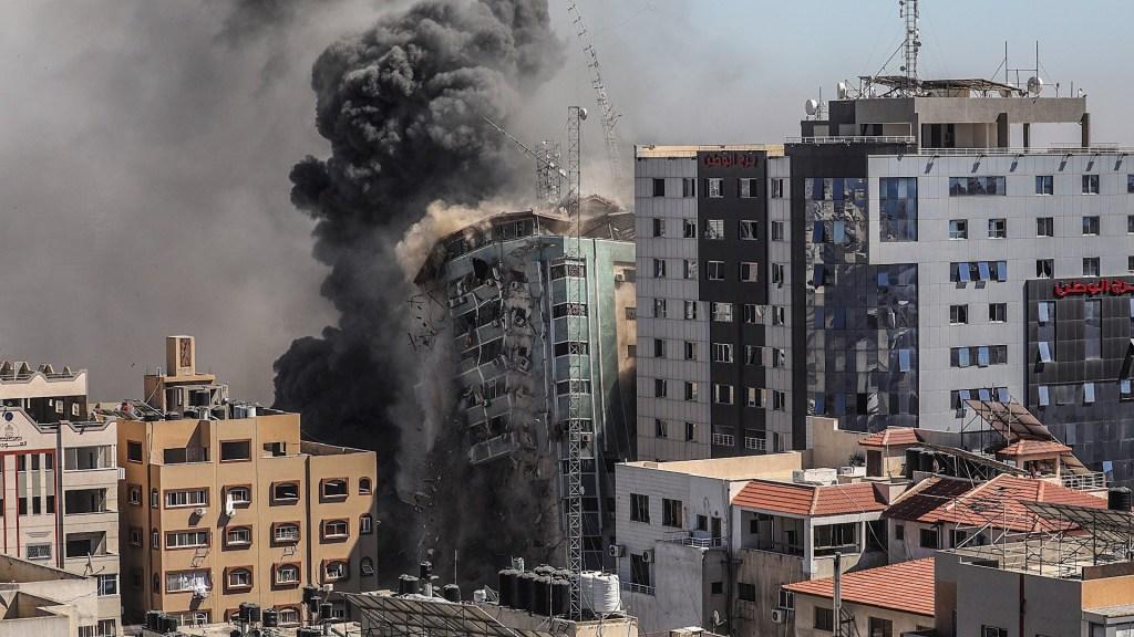 Una columna de humo asciende de una torre de 14 plantas en la ciudad de Gaza, sede de la agencia de noticias estadounidense AP, la cadena de noticias Al Jazeera y otros medios internacionales, que Israel derribó este sábado. Foto de EFE/ Mohammed Saber.