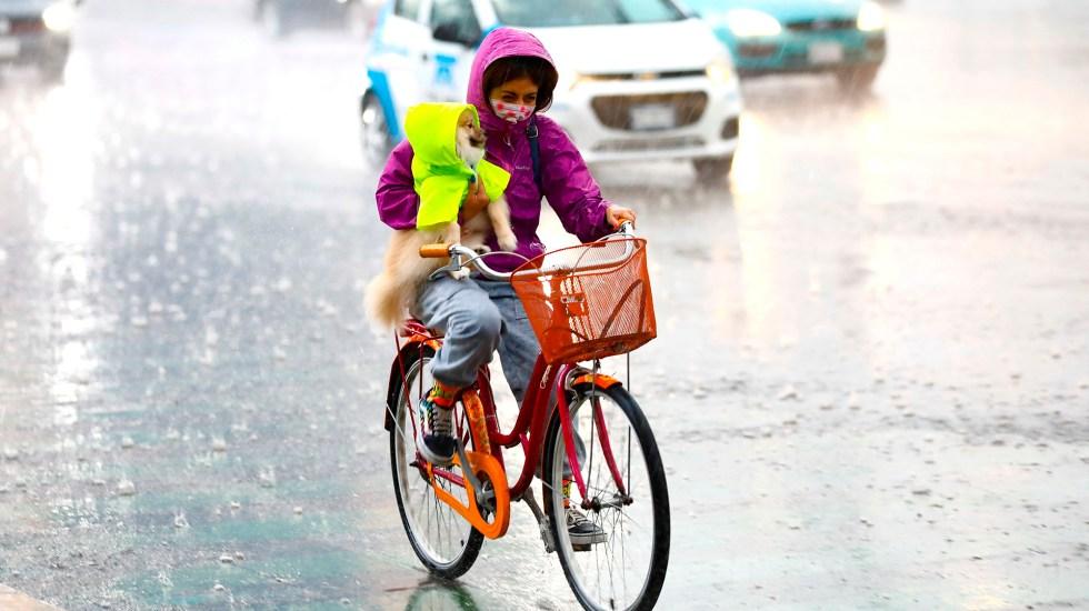 Activan Alerta Amarilla por lluvias en 10 alcaldías - Mujer bajo la lluvia con su perro. Foto de EFE