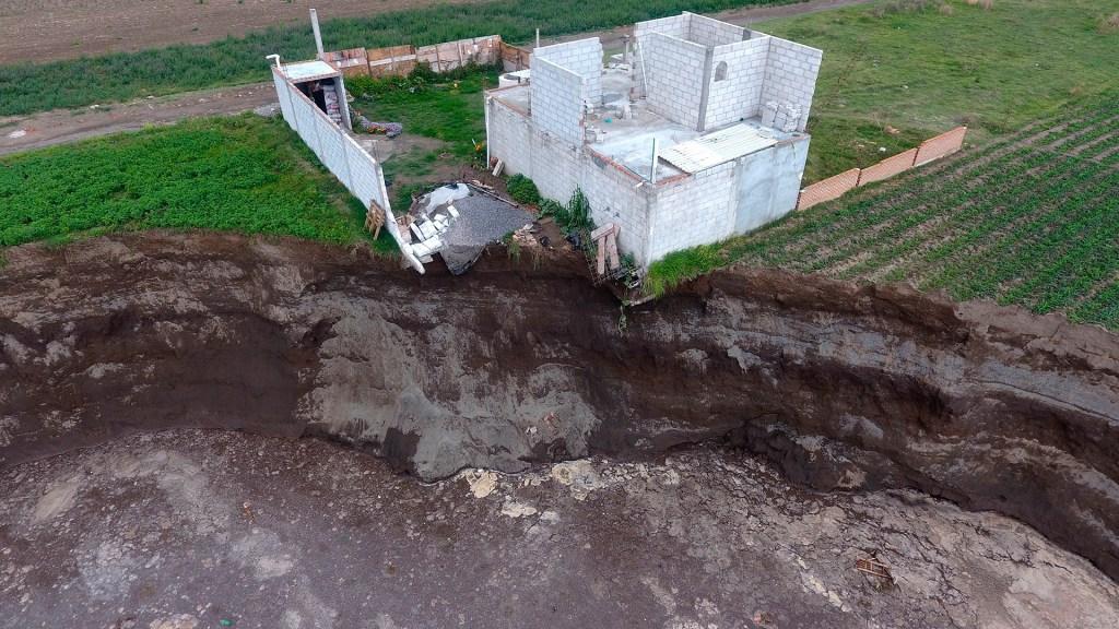 Familia cuya casa colapsó en socavón de Puebla ha rechazado opciones de terreno - El gran socavón aparecido hace casi una semana en el municipio de Juan C. Bonilla de Puebla siguió extendiéndose y provocó el derrumbe de una barda y de una recámara de la casa ubicada en el borde del agujero. Foto de EFE