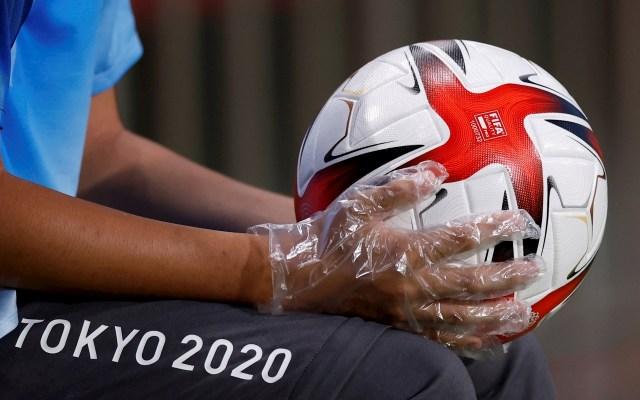 Fútbol: Brasil – Egipto - Un recogepelotas con guantes de plástico en las manos sostiene un balón durante el encuentro de cuartos de final entre las selecciones de Brasil y Egipto, durante los Juegos Olímpicos 2020, en el Estadio de Kashima. Foto de EFE/ Fernando Bizerra.