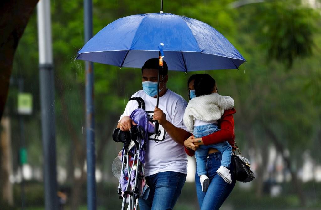Huracán Linda crece a Categoría 4, pero se aleja de México - Una familia se protege de la lluvia, en Ciudad de México. Foto de EFE/ Carlos Ramírez/ Archivo. lluvias