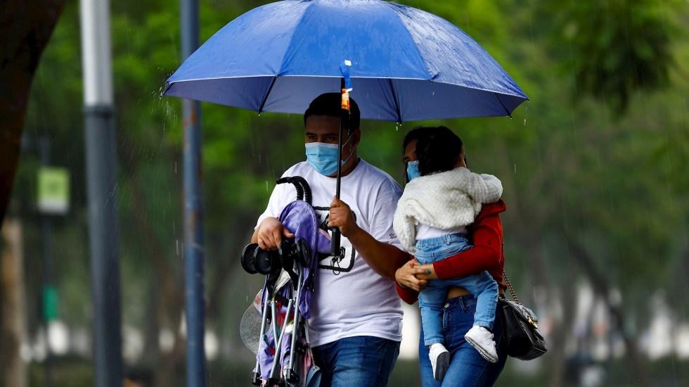 Alerta Amarilla en 11 alcaldías de la Ciudad de México por lluvias - Una familia se protege de la lluvia, en Ciudad de México. Foto de EFE/ Carlos Ramírez/ Archivo. lluvias