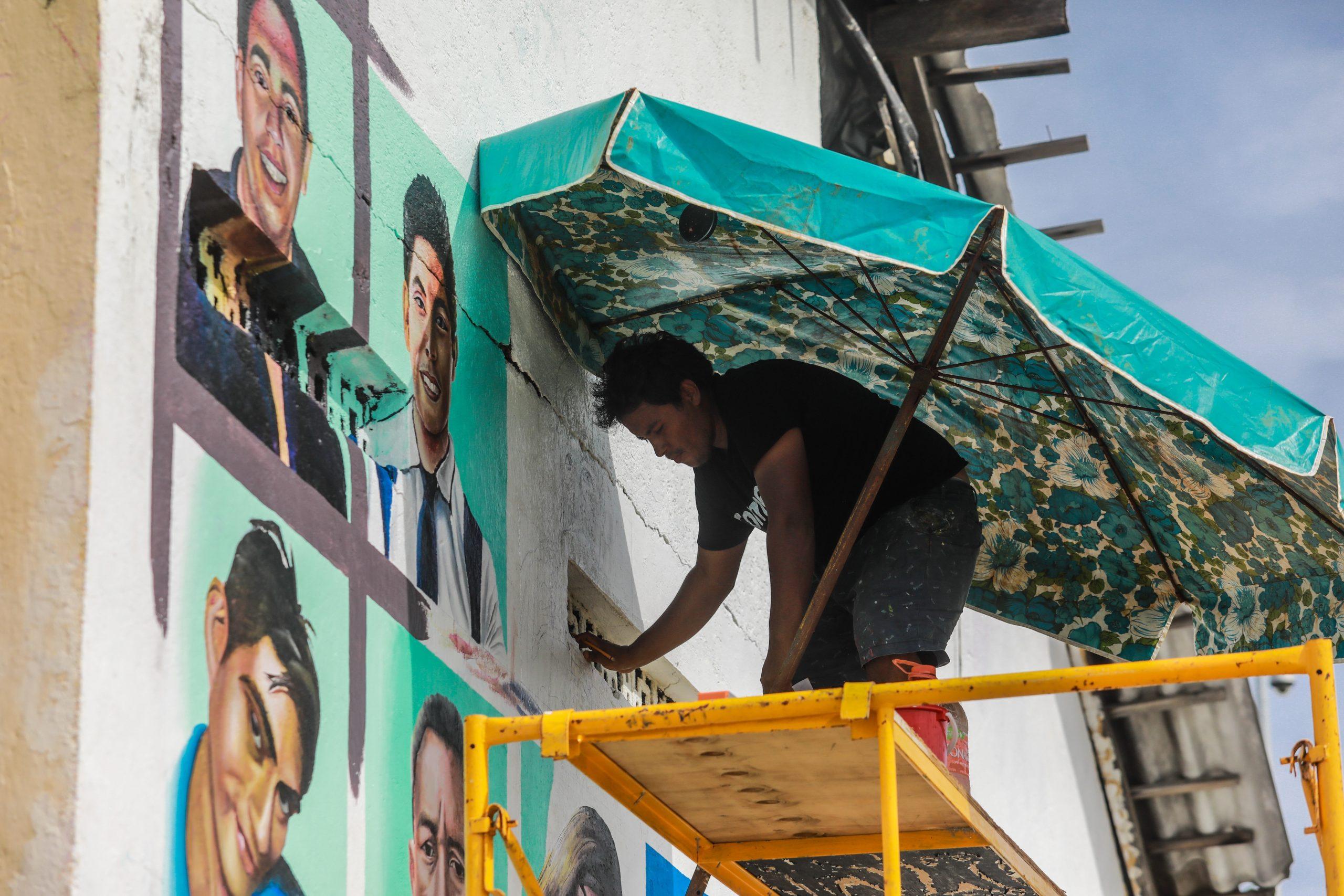 El artista Alexis Godínez Rodríguez pinta rostros de personas desaparecidas sobre un mural en Acapulco. Foto de EFE/ David Guzmán.