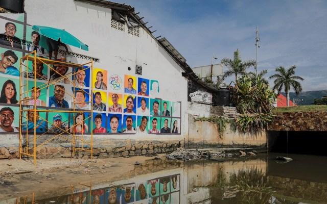 Con mural, pintan rostros de desaparecidos en playa de Acapulco - El artista Alexis Godínez Rodríguez pinta rostros de personas desaparecidas sobre un mural en Acapulco. Foto de EFE/ David Guzmán.