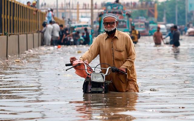 Lluvias monzónicas en Karachi - Un hombre empuja su motocicleta por una calle inundada tras las fuertes lluvias en Karachi, Pakistán, este jueves. Foto de EFE/ EPA/ SHAHZAIB AKBER.