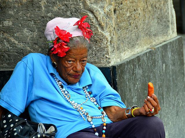 Una interesante dama espera en la parada del autobús en la Habana, Cuba.