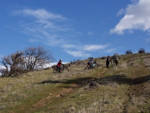looking up an incredibly steep hillside with a handful of cyclists pushing bikes up the rutted trail