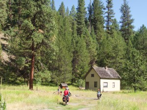 kids pedaling into a clearing to check out the 1930's era partly boarded up guard station at the other side of the clearing.