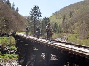 three upright bicyclists pedal towards the camera on a train trestle turned multi-use trail.