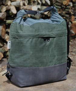 Canvas bag with brown bottom green middle and blue top rolled and connected with 2 metal clips and black strap dangling on side, on top of tree trunk