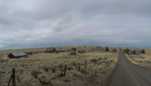 wide-angle perspective of an old and somewhat kept up homestead on an expansive grass prairie