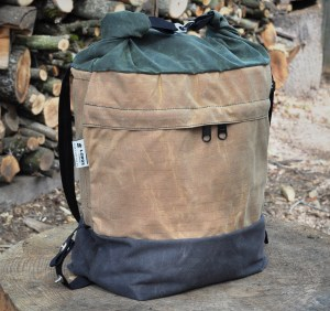 Canvas bag with brown bottom light brown middle and green top rolled and connected with 2 metal clips and black strap dangling, on top of tree trunk