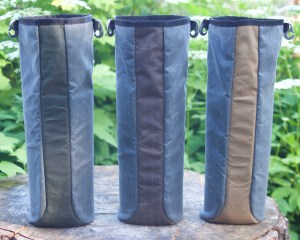 Left bag blue w green strip down center and open at top, middle bag blue w brown strip and open at top, right bag blue w tan strip and open at top, all atop tree stump