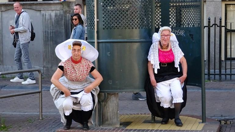 Christien Zuidweg (links) en Suzan Heere (rechts) in Zeeuwse klederdracht bij krul-urinoir in Amsterdam (foto: Jac van Belzen)