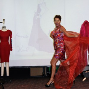 Lorelei Shellist, iMage COnsultant, on stage wearing a colorful dress and flowing scarf, mannequin with red dress