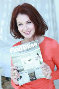 Lorelei Shellist, contributing author, holding an issue of Find Bliss Magazine