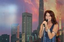 Host Emcee Lorelei Shellist holding microphone, Los Angeles backdrop
