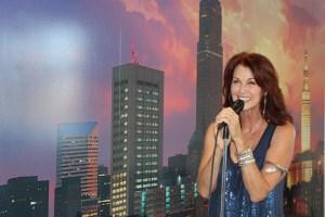 Lorelei Shellist holding microphone, Los Angeles backdrop