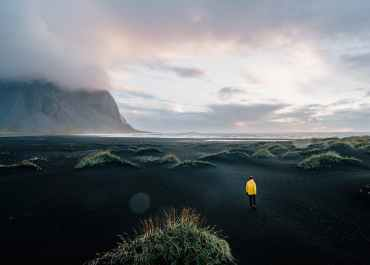 person in yellow jacket standing on green grass field near mountain