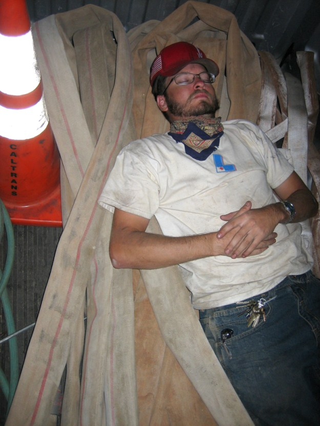 Sean, sleeping in the back of his truck, on top of fire hoses, next to a safety cone, at midnight. I think this pic speaks for itself.