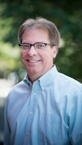 A white man with brown hair and glasses wears a blue button up and smiles to the camera