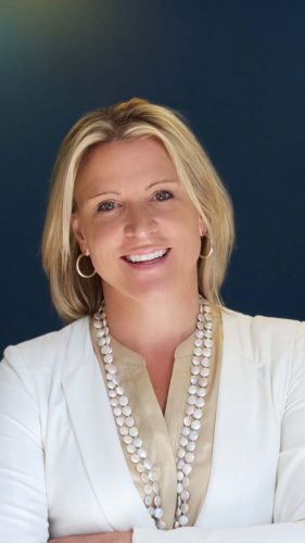 A white woman with blonde hair and a white blazer smiles to the camera in front of a dark blue background.