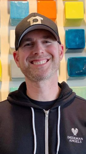 A white man with a black baseball cap and hoodie smiles to the camera.