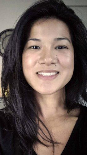 A photo of a woman with black hair and a black v-neck smiles to the camera.