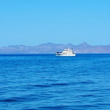A boat off the Loreto Bay coast with Isla Carmen in the background.