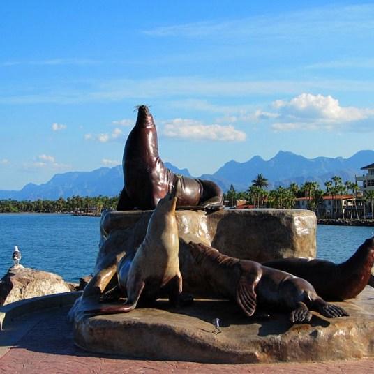 A statue of seals in the Loreto marina.