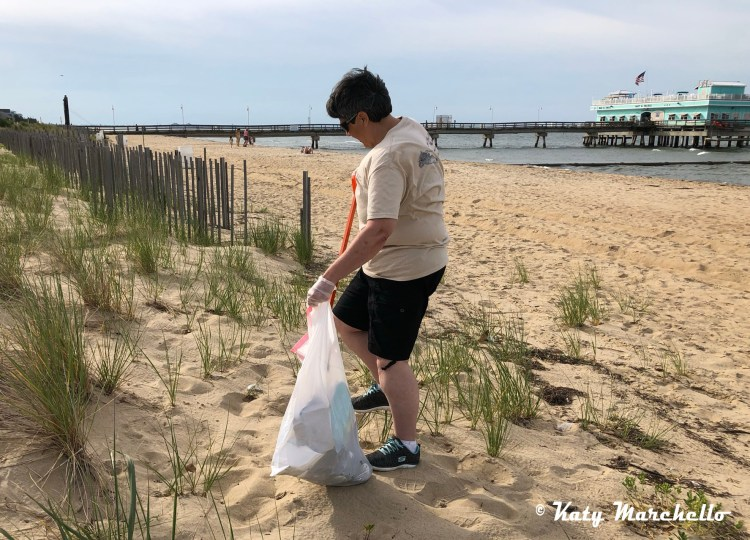 Lori A Cash picking up litter on the beach at Ocean View Fishing Pier in Norfolk, Virginia as a participant in Beachside Litter Challenge held by Keep Norfolk Beautiful.