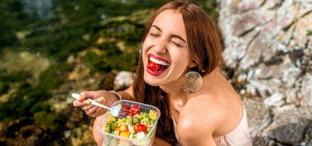This young woman is enjoying her healthy raw food lunch for her gut-brain axis and gut microbiome.