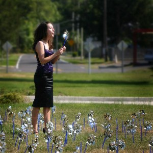 A relaxed lady blows a dandelion in a field after ketamine IV, IM, or IN for depression.