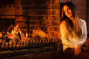 Woman relaxed by fire due to IV ketamine treatment beats SAD seasonal affective disorder.