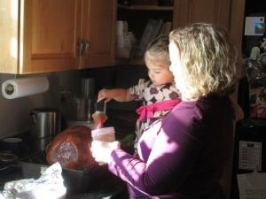 Zinnia helping her Bubie with the final glaze on the Thanksgiving turkey.