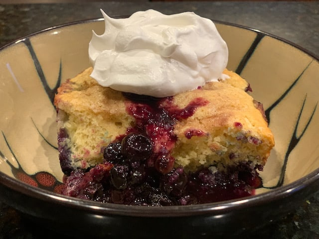 blueberry cobbler in a bowl with whip topping.