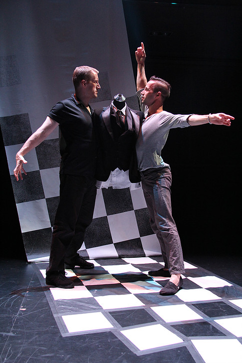 Two men in ballroom dancing positions, with a tuxedo jacket on a mannequin behind them.