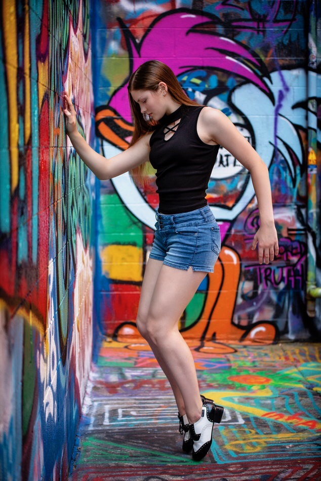 A teen girl standing by a colourfully graffitied wall, wearing tap shoes.